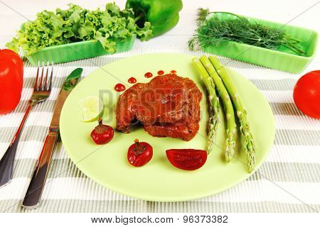 roast stew beef pork meat served with vegetables on green plate and cutlery on napkin over wooden table with red hot peppers