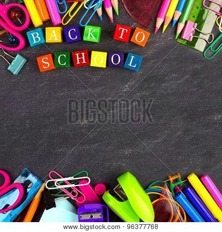 Back to School wooden blocks with school supplies frame on blackboard