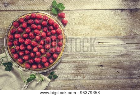 Tart with raspberries on a wooden background with space for text. top view