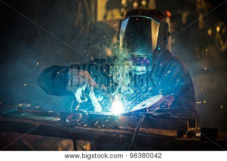 Welder in action with bright sparks. Construction and manufacturing theme.