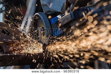 Grinding machine in action with bright sparks. Construction and manufacturing theme.