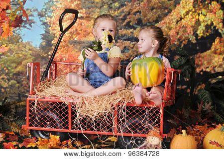 Two preschool sisters sitting with a sunflower and pumpkin in a work wagon surrounded by colorful fall trees.