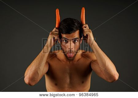 Young man devil with horns carrots
