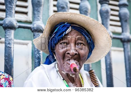 Portrait of african cuban woman smoking cigar and looking at camera