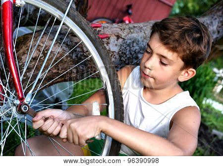 cute preteen boy make rapairment of his bisycle