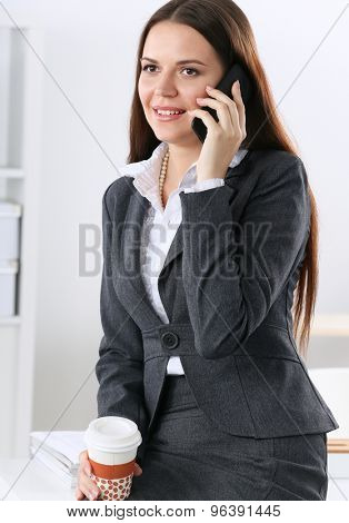 Smiling businesswoman talking on the phone at the office .
