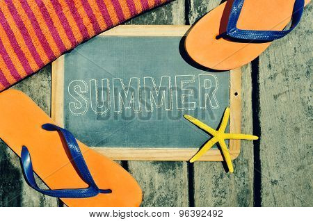 high-angle shot of a rustic wooden surface with a starfish, a beach towel, a pair of flip-flops and a chalkboard with the word summer written in it
