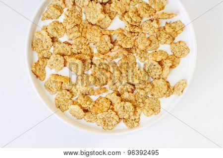 high-angle shot of a white bowl with breakfast cereals soaked in milk on a white table
