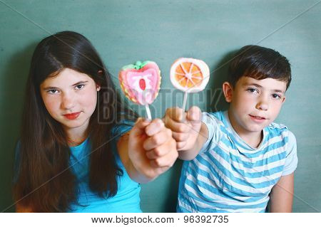 siblings  with fruit  marsh mellow candies on stick