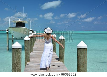 Girl on the wooden jetty looking to the ocean. Great Exuma, Bahamas