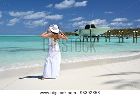 Girl on the beach looking to the ocean. Great Exuma, Bahamas