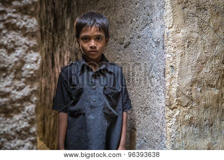 MUMBAI, INDIA - 12 JANUARY 2015: Young Indian boy from Dharavi slum stands in empty narrow street in black shirt.