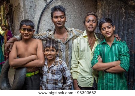 MUMBAI, INDIA - 12 JANUARY 2015: Five Indian boys from Dharavi slum stand in street. Dharavi is one of the largest slums in the world.