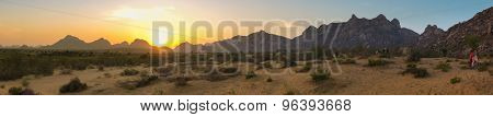 GODWAR REGION, INDIA - 15 FEBRUARY 2015: Panorama of desert scene with mountain range in sunset with people in distance.
