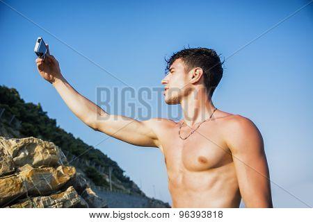 Shirtless Young Man Taking Selfie Photos at the Beach