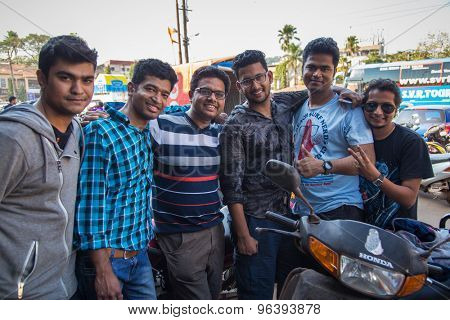 GOA, INDIA - 27 JANUARY 2015: Six Indian men stand together in street next to parked vehicles.