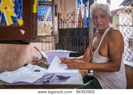 MUMBAI, INDIA - 16 JANUARY 2015: Elderly Indian man sits outdoors in front of home and punches holes into business paper.