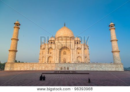 AGRA, INDIA - 28 FEBRUARY 2015: View of Taj Mahal from East side. Couple sit and look at Taj with dog sitting on other side.