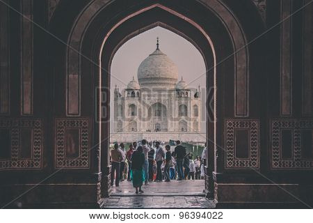 AGRA, INDIA - 28 FEBRUARY 2015: View of Taj Mahal from inside the Great Gate with visitors. Post-processed with grain, texture and colour effect.