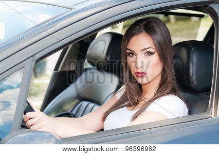 Young beautiful girl sitting and driving a black car