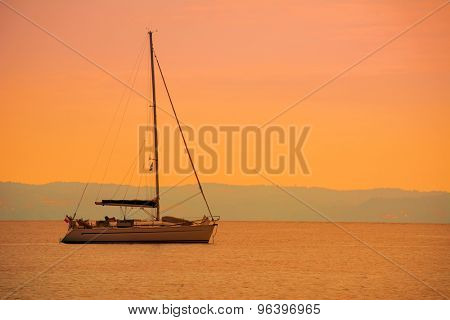 Lonely sailboat on the sea at sunset