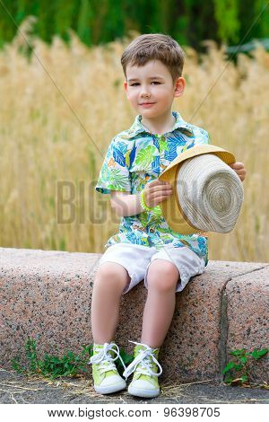 Smiling young fashion boy holding his hat while looking down, posing