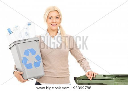 Woman holding a recycle bin and standing by a large trash can isolated on white background