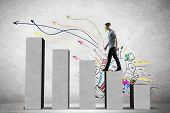 picture of step-up  - Young businessman stepping up on chart bar - JPG