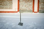 picture of shovel  - Shovel in snowdrift on a background of a brick wall - JPG