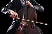 picture of cello  - Man playing on cello on dark background - JPG