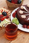 image of hot-chocolate  - whole big chocolate cream brownie cake topped with white chocolate and cream flowers with hot tea cup decorated with fruits apple plum and grape on plate on wooden table - JPG