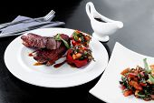 pic of braai  - fresh red beef meat steak barbecue garnished vegetable salad and basil on white plate over black wooden table with bbq sauce in sauceboat - JPG
