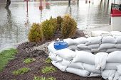 picture of sandbag  - A pile of sandbags stacked to protect a restaurant on a cloudy day - JPG