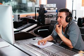 image of studio  - Hispanic sound engineer working at mixing panel in the recording studio - JPG