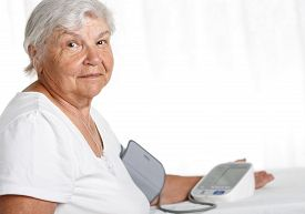 stock photo of manometer  - Elder woman measuring blood pressure with automatic manometer at home - JPG