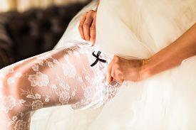 foto of garter-belt  - bride dresses garter on the leg - JPG