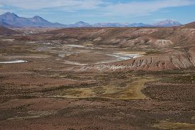 stock photo of open grazing area  - Large open plain created by the River Lauca in Lauca National Park - JPG
