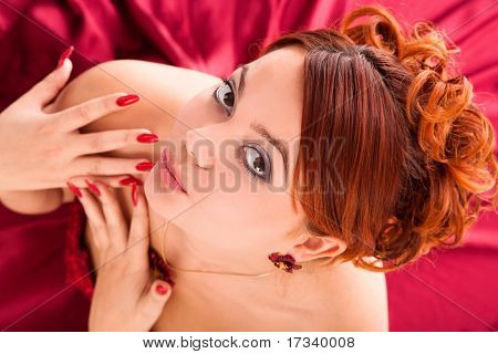 young attractive woman sitting in long red dress on red background. view from above.