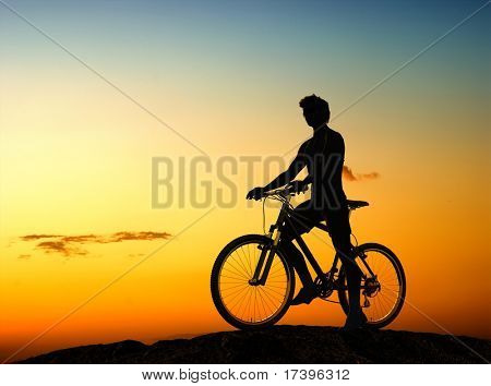 Silhouette of man on a bicycle  on a background landscape