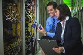 Technicians using digital cable analyzer while analyzing server in server room poster