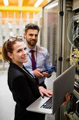 Portrait of technicians using laptop while analyzing server in server room poster