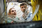 Technicians fixing cable in server room poster