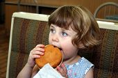 stock photo of obesity children  - Little girl eating hamburger in fast food restaurant - JPG