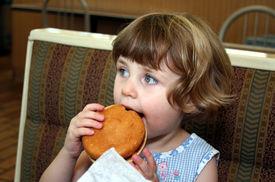 stock photo of obese children  - Little girl eating hamburger in fast food restaurant - JPG