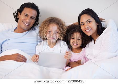 Young family together on the bed with laptop