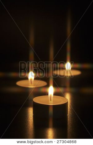 Closeup of burning candles on black background