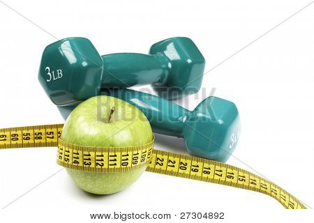 Fresh appetizing apple and brightly colored dumbbells tied with a measuring tape