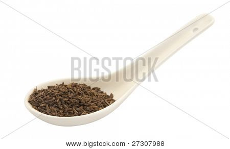 cumin seeds in a ceramic spoon, isolated on a white background.