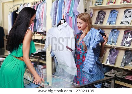 Girl seller helps shoppers choose the clothes in the store
