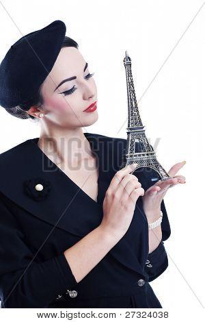 bella joven sostenga símbolo de París torre eiffel aislado sobre fondo blanco y que representa a t